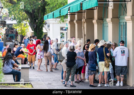 New Orleans, USA - April 23, 2018: People standing in line queue during day for famous Cafe Du Monde restaurant beignet powdered sugar donuts and coff - Stock Photo