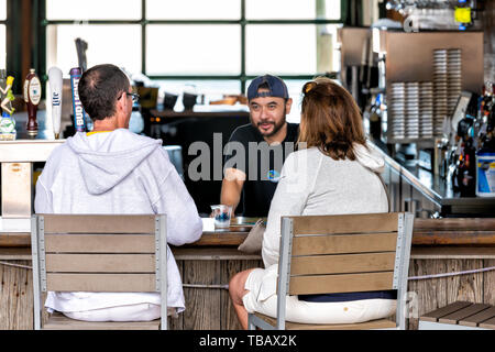 Destin, USA - April 24, 2018: Inside of Margaritaville restaurant with mature couple sitting at bar counter, bartender serving alcoholic drink in Harb - Stock Photo