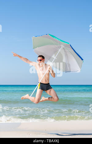 Young happy smiling attractive fit man jumping in air on beach on sunny day with red sunglasses in Florida panhandle with ocean, holding umbrella - Stock Photo