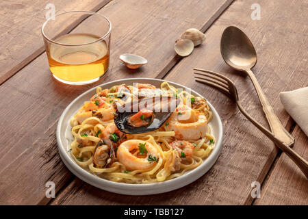 Seafood pasta. Tagliolini with mussels, shrimps, clams and squid rings, with a glass of wine on a dark rustic wooden background - Stock Photo