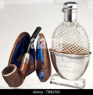 Paul von Hintze (1864 - 1941) - a liquor bottle and a shag pipe Silver-mounted bottle, dated 1898. Flat oval glass body, the upper third with diamond-cut. Solid, folding silver lid and removable silver drinking cup, gilt interior, engraved exterior with dedication 'Grumme s/l P. Hintze 1898' and stamped at the base with crown, crescent moon, '800' and '17944'. Signs of age. Height 14.5 cm. With a shag pipe (by 'BBB') with real wood pipe bowl, silver shoulder (embossed) and black plastic mouth piece, in leather case with blue velvet lining, exteri, Additional-Rights-Clearance-Info-Not-Available - Stock Photo
