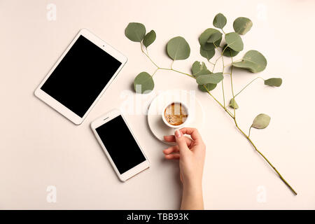 Female hand with cup of coffee, tablet computer and mobile phone on light background - Stock Photo