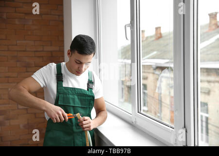 Young worker cutting seal for installation of new window - Stock Photo