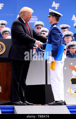 Donald J. Trump, President of the United States, congratulates Cadet 1st Class Trey Landon Arnold, the Class of 2019 top grad, at Falcon Stadium during the U.S. Air Force Academy Class of 2019 Graduation Ceremony at the Academy's Falcon Stadium in Colorado Springs, Colo., May 30, 2019. Nine-hundred-eighty-nine cadets crossed the stage to become the Air Force's newest second lieutenants. (U.S. Air Force photo/Darcie L. Ibidapo) (released) - Stock Photo