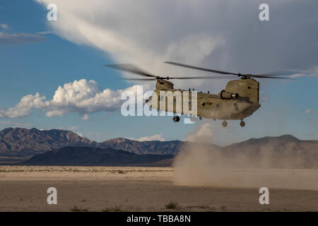 A CH-47F Chinook prepares to land as Oregon Army National Guard pilots from the 1-168th General Support Aviation Battalion, perform multiple dust landing certification flights at the National Training Center (NTC) in Fort Irwin, Calif., May 29, 2019. B Co. 1-168th General Support Aviation Battalion is providing air lift capabilities and support to the 116th Cavalry Brigade Combat Team. A month-long NTC rotation provides more than 4,000 service members from 31 states, including units from 13 National Guard states and territories, with realistic training to enhance their combat, support and sust - Stock Photo