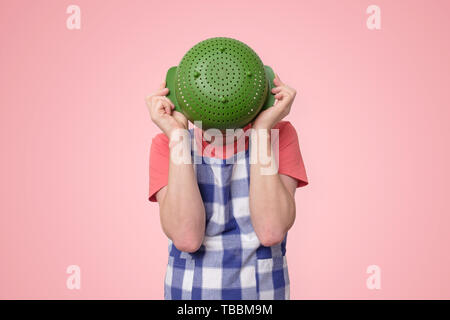 Man in apron holding colander near face hiding. - Stock Photo
