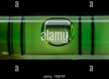 Green bubble level macro, isolated on a black background. Shallow depth of field - Stock Photo