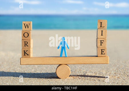 Blue Human Figure Standing Between The Work And Life Blocks Balancing On Seesaw At Beach - Stock Photo