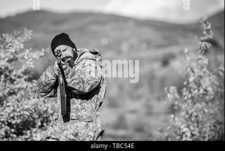 Man brutal gamekeeper nature background. Hunter hold rifle. Bearded hunter spend leisure hunting. Focus and concentration of experienced hunter. Regulation of hunting. Hunting masculine hobby concept. - Stock Photo