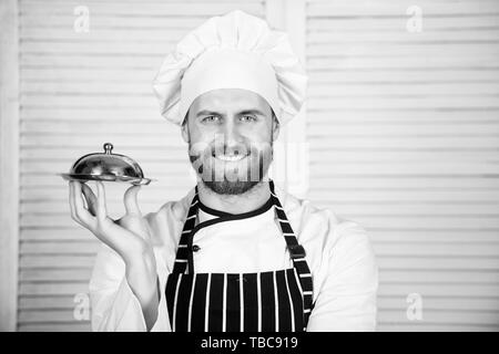 Chefs dish. Man cook hat and apron hold meal covered with lid. Delicious meal presentation. Haute cuisine characterized meticulous preparation and careful presentation meal. Secret meal presentation. - Stock Photo