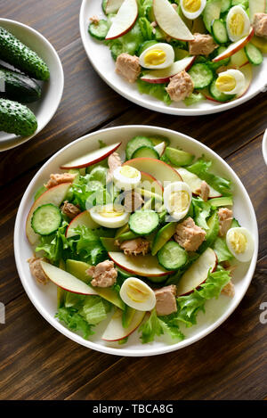 Tuna salad with slices of cucumber, avocado, red apple and eggs in bowl on wooden background. Healthy diet food. - Stock Photo