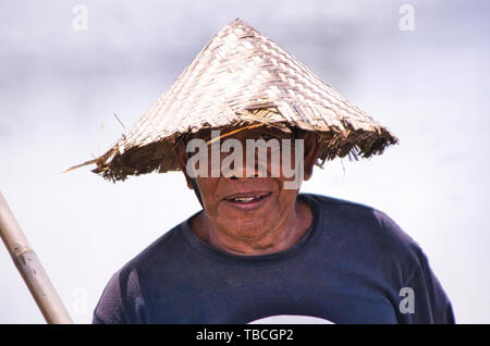 UBUD, BALI, INDONESIA - FEBRUARY Circa, 2019. An unidentified Indonesia man who living at out of the town of Ubud who wearing leaf hat and looking cam - Stock Photo