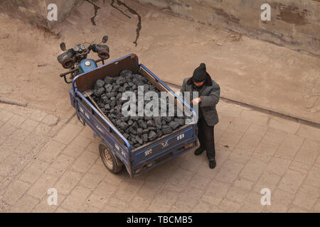Chinese man standing by a 3 wheel motorcycle carrying coal in the ancient city of Pingyao. Top view seen from above. Pingyao, China - December 26, 201 - Stock Photo