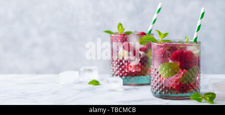 Raspberry cocktail, fizz, lemonade, ice tea with fresh mint on marble background. Copy space. - Stock Photo
