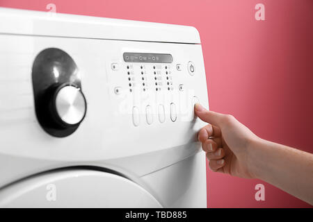 Woman switching on washing machine, closeup - Stock Photo