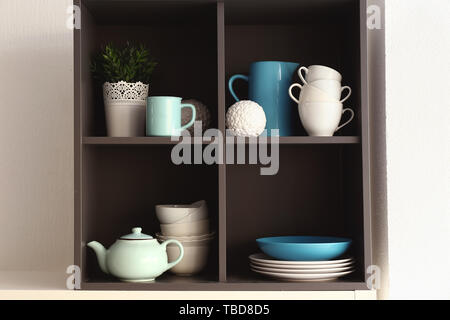 Open cupboard with clean dishes in kitchen - Stock Photo