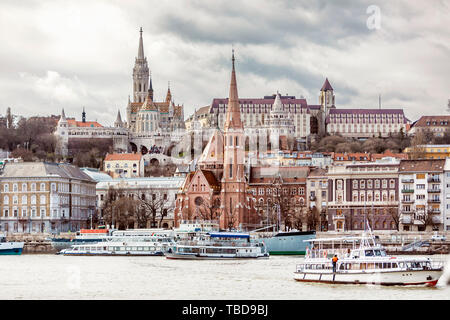 View of Fisherman's Bastion and the church of St. Matthias from the east side of Danube with motor ships on it - Stock Photo