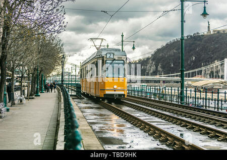 BUDAPEST, HUNGARY - 24 August, 2018: Retro yellow tram in Budapest in Hungary riding on the rails in a on a cloudy spring day - Stock Photo