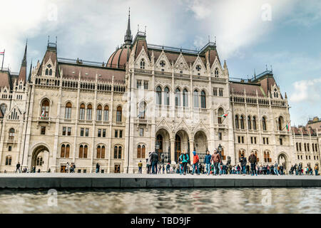 BUDAPEST, HUNGARY - 24 August, 2018: Tourists on the coast of Danube river near the Hungarian Parliament Building - Stock Photo