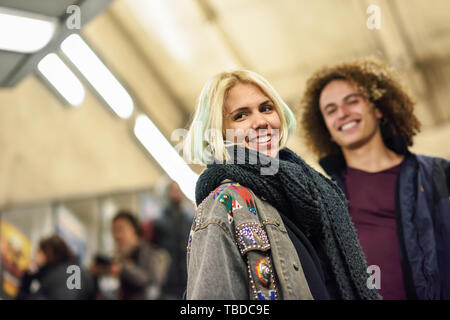 Young couple going upstairs at a subway station. - Stock Photo