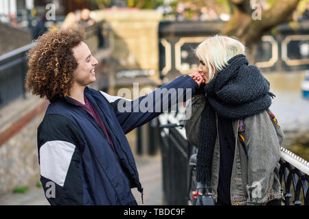 Young woman kissing the hand of her boyfriend in Camden Town Little Venice, - Stock Photo