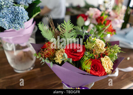 In the foreground a bouquet in a vase on the background of a flower shop. People work, Profession florist. Summer bouquet. Flowers delivery - Stock Photo