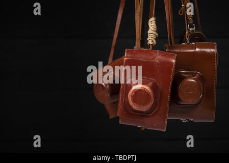 Drohobych, Ukraine - 03 February, 2019: Heap of 35mm retro cameras in leather covers on black, top view