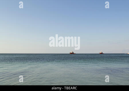 Fishing trawlers in the vastness of the ocean, sailing off the coast of Antofagasta, Chile. - Stock Photo