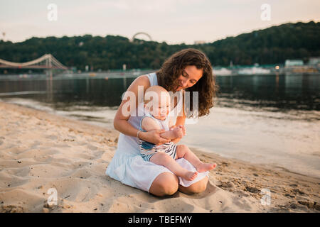 Young mother sitting on the beach with one year old baby son. Boy hugging, smiling, laughing, summer day. Happy childhood carefree game on the open - Stock Photo