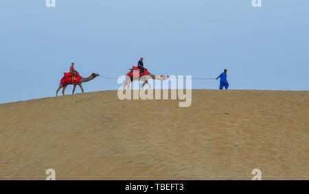Jaisalmer, India - Nov 8, 2017. Riding camel on Thar Desert in Jaisalmer, India. Thar Desert is a large arid region in the northwestern part of the In - Stock Photo