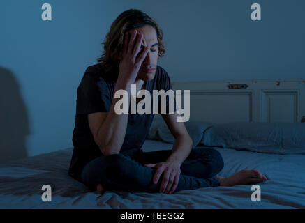 Devastated millennial man crying sad feeling hurt and hopeless suffering Depression. Depressed teenager victim of bullying or abuse sitting on bed alo