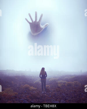Young woman facing a giant creature that hides on the fog - Stock Photo