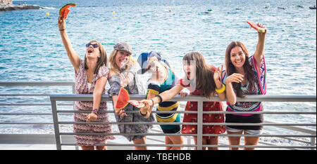 Group of crazy females friends have fun outdoor with watermelon and friendship - people on vacation enjoy and laugh a lot with joyful together - blue  - Stock Photo