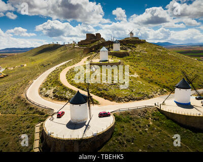 Scenic view from drone of ancient windmills and castle ruins atop Cerro Calderico ridge, Consuegra, Spain - Stock Photo