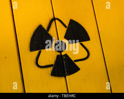 Radioactivity sign, close-up. Sign of radiation on a yellow wooden board. Radioactive sign - symbol of radiation. Yellow and black radioactive hazard, - Stock Photo