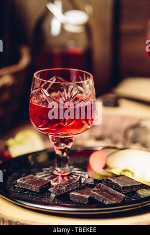 Glass of homemade redcurrant nalivka with apple slices and chocolate on metal plate - Stock Photo