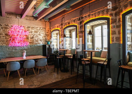 Neon sign on wall in interior of cafe - Stock Photo