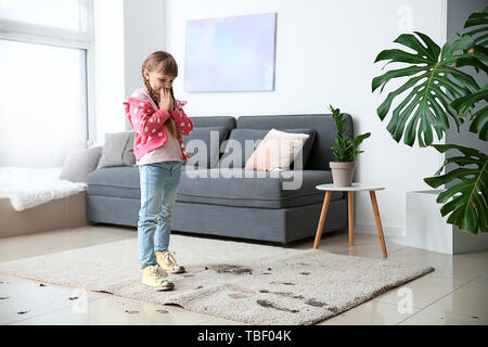 Little girl in muddy shoes messing up carpet at home - Stock Photo