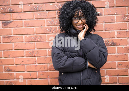 Portrait of young curly african woman standing in front of brick wall. - Stock Photo