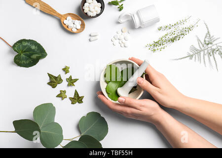 Female hands with mortar, different herbs and plant based pills on white background - Stock Photo