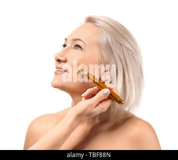 Mature woman receiving facial massage on white background - Stock Photo