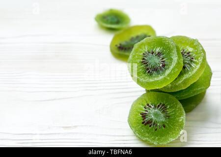 Tasty dried kiwi on white wooden background - Stock Photo
