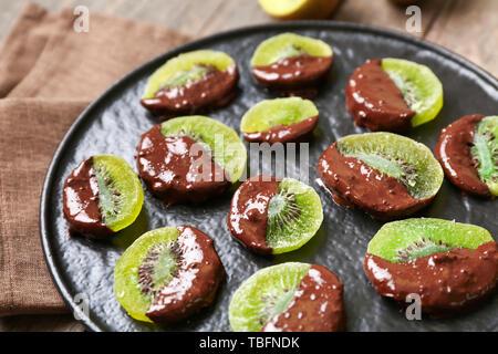 Tasty chocolate covered kiwi on plate, closeup - Stock Photo