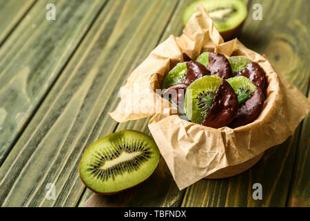 Tasty chocolate covered kiwi on wooden table - Stock Photo