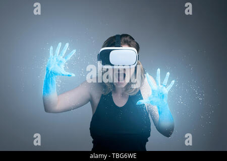Girl using VR gadget with hands turning into ice in a virtual cyber simulator