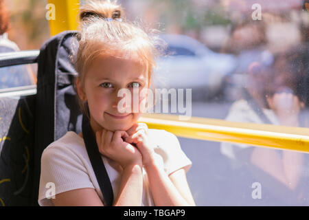 A little girl is going by bus. Schoolgirl sitting in school bus and ready for her first ride. - Stock Photo