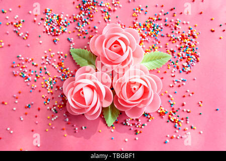Arrangement of flowers and confetti to decorate sweet pastries. Top viewe, flat lay - Stock Photo