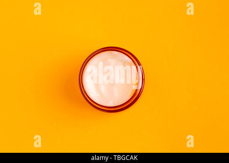 Face cream in a yellow glass in Open jar on a yellow background. Top view. - Stock Photo
