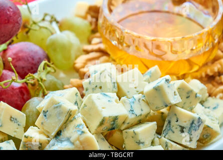 Different kinds of cheese, grapes, walnuts and honey gourment assorted close-up - Stock Photo