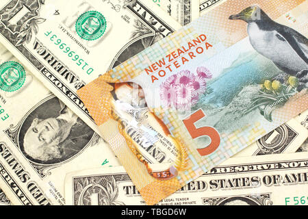A close up image of a New Zealand five dollar bill with United States one dollar bills in macro - Stock Photo